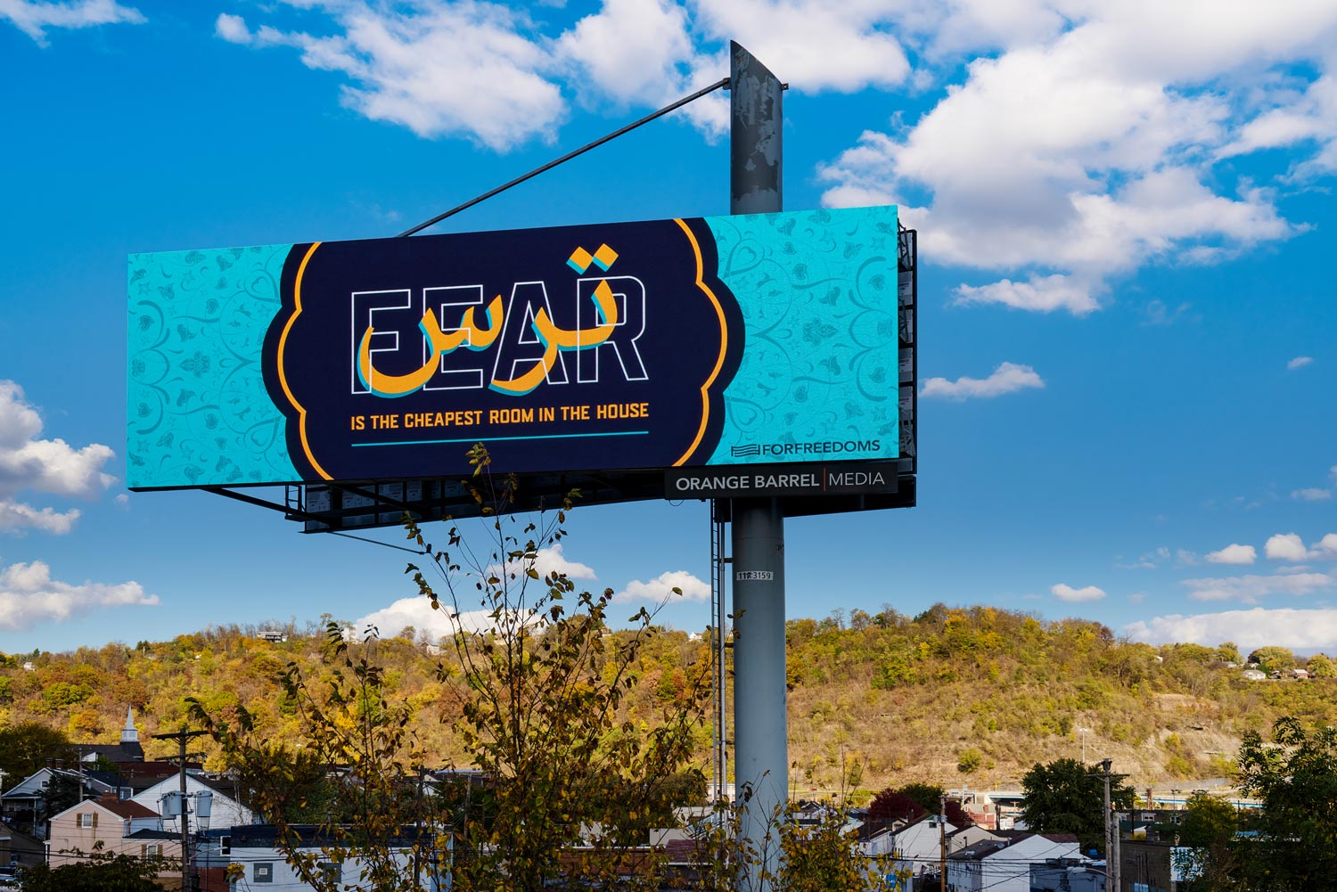Photograph of billboard on the side of a highway in front of a grassy hill and a blue sky with white fluffy clouds. The billboard has a teal floral background. Text on a dark blue background in the center reads Fear is the Cheapest Room in the House.