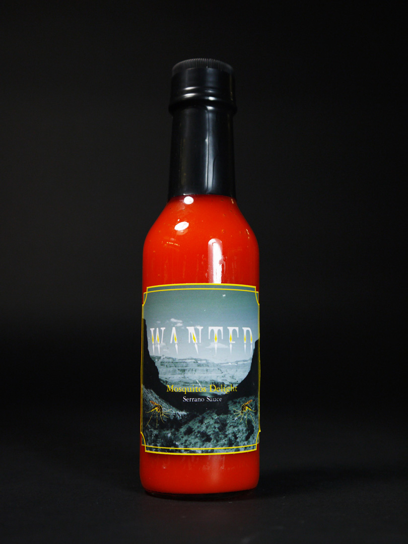 Photo of a hotsauce bottle with yellow trim and the label saying, 'Mosquitos Delight' over a black and white image of a desert landscape and photos of yellow mosquitos on the sides.