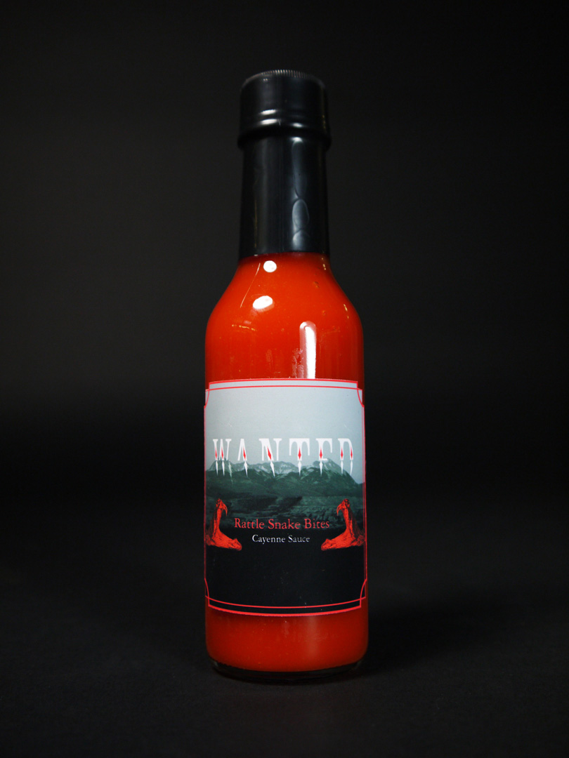 Photo of a hotsauce bottle with red trim and the label saying, 'Rattle Snake Bites' over a black and white image of a desert landscape and photos of red rattlesnakes on the sides.