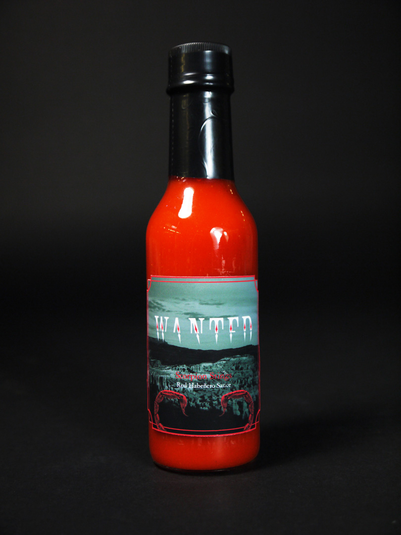 Photo of a hotsauce bottle with dark red trim and the label saying, 'Scorpion Stings' over a black and white image of a desert landscape and photos of dark red scorpion tails on the sides.