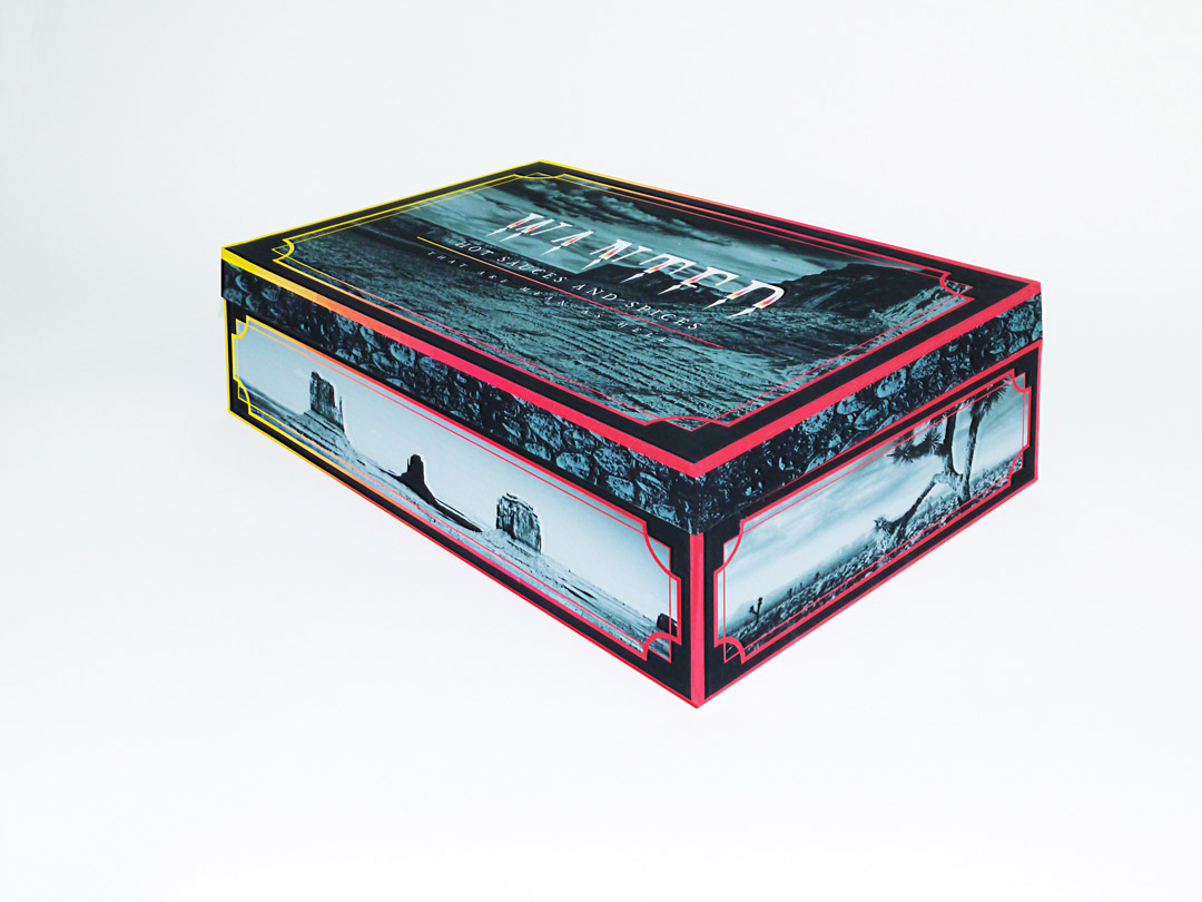 Angled photo of the front right corner of the Wanted box. On the sides of the lid is a black and white snake skin pattern. On each side of the box is a different black and white photo of a desert landscape.